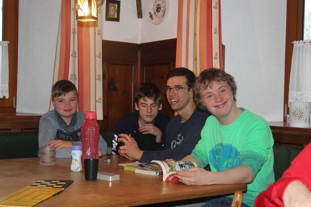 vier Jungs sitzen am Tisch und spielen