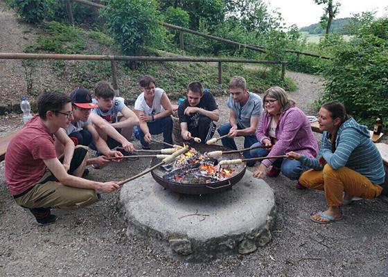 Gruppe die um ein Lagerfeuer Stockbrot grillen