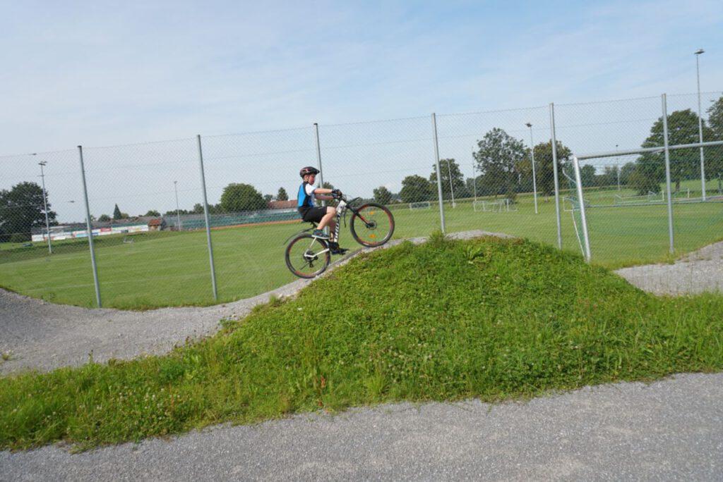 Junge fährt mit seinem Fahrrad einen Buckel hinauf