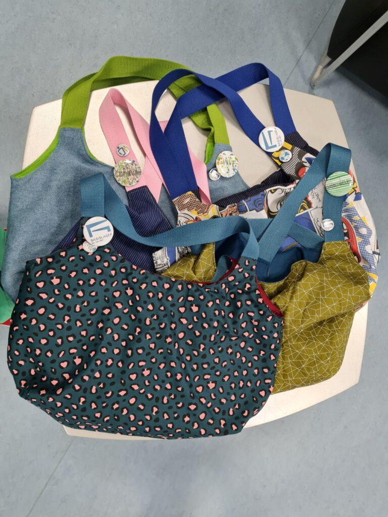 mehrere bunte Stofftaschen mit den Buttons