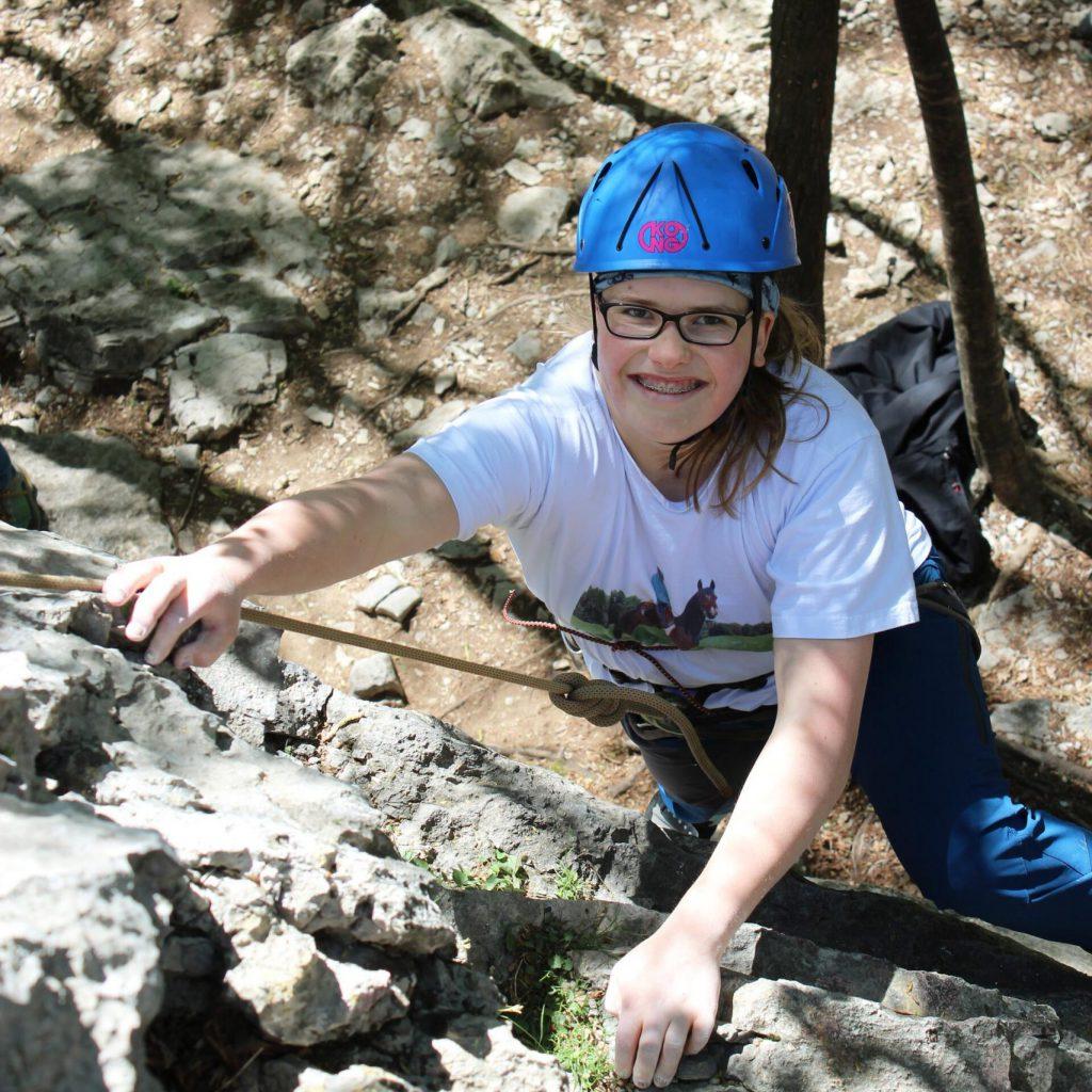 Mädchen mit Brille und Helm steigt in den Fels ein