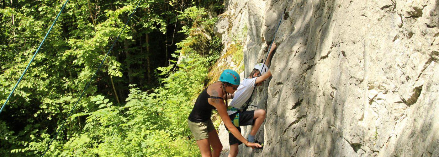 Trainerin hilft Jungen den Fuß am Fels zu plazieren