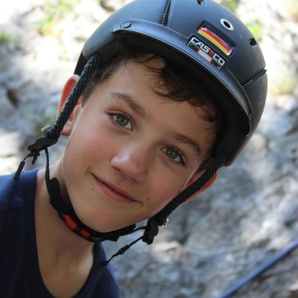 Junge mit schwarzem Helm vor Felswand