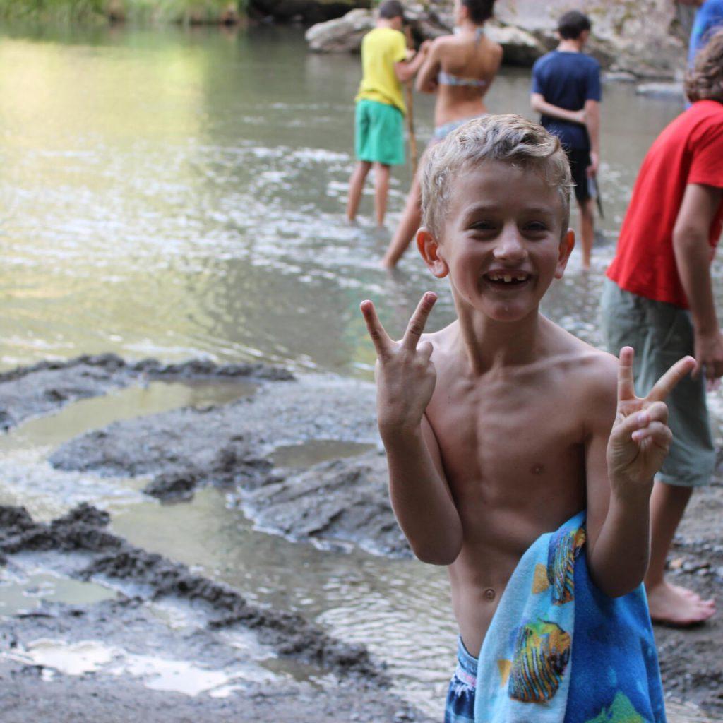 Junge in Badehose macht doppeltes Victoryzeichen