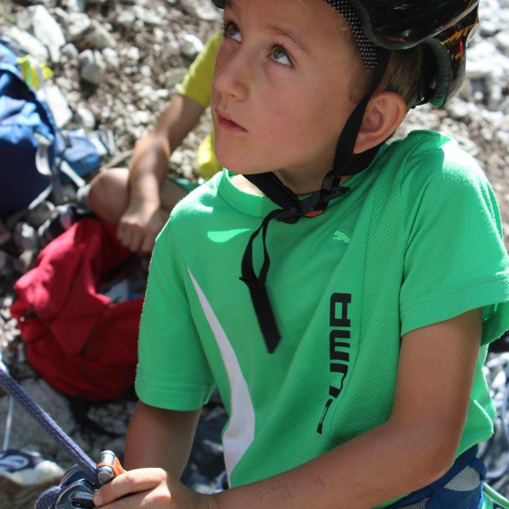 Junge mit Helm studiert den zu kletternden Felsen