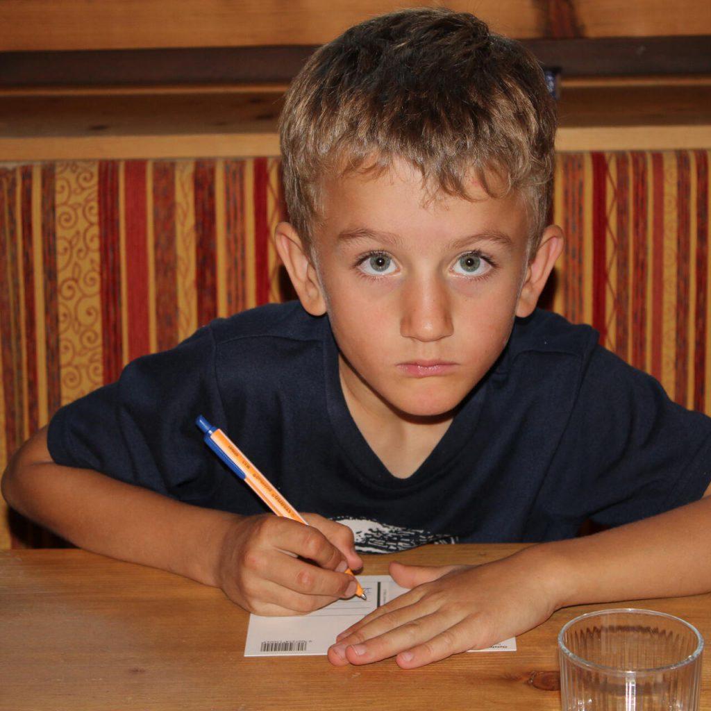 Junge am Tisch schreibt eine Postkarte